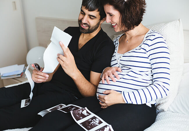 Pregnant couple looking at sonograms